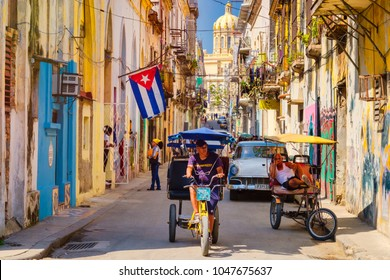 HAVANA,CUBA - MARCH 16,2018 : Urban scene with cuban flag and colorful decaying buildings in Old Havana