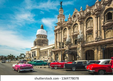 HAVANA,CUBA - MARCH 18,2019: Colourful old American taxi cars parked outside the Gran Teatro de La Habana and El Capitolio, Havana, La Habana, Cuba, West Indies, Caribbean, Central America