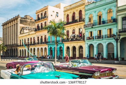 HAVANA,CUBA - MARCH 18,2019: Colourful old American classic taxi cars driving outside El Capitolio in Havana, La Habana, Cuba, West Indies, Caribbean, Central America