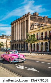 HAVANA,CUBA - MARCH 18,2019: A pink American classic car next to El Capitolio in Havana, La Habana, Cuba, West Indies, Caribbean, Central America