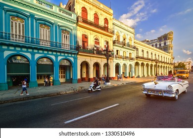 HAVANA,CUBA - MARCH 3,2019 : Classic car and colorful buildings in downtown Havana at sunset