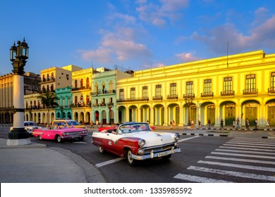 HAVANA,CUBA - MARCH 3,2019 : Classic cars and colorful buildings in downtown Havana at sunset