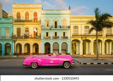 HAVANA,CUBA - MARCH 3,2019 : Classic convertible car and colorful buildings in downtown Havana at sunset