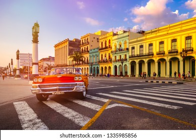 HAVANA,CUBA - MARCH 3,2019 : Red classic convertible car and colorful buildings in downtown Havana at sunset