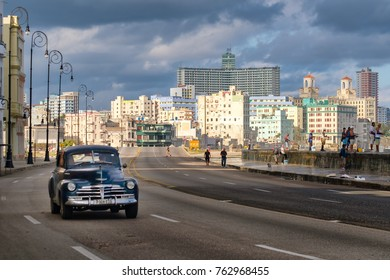 HAVANA,CUBA - NOVEMBER 25,2017 : Urban scene with old car at the famous Malecon seawall in Havana