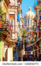 HAVANA,CUBA - SEPTEMBER 14,2018 : Colorful street in Old Havana with the Presidential Palace on the background