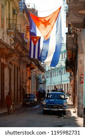 HAVANA,CUBA - SEPTEMBER 29,2018 : Urban scene with cuban flags, antique cars, people and aged buildings in Old Havana