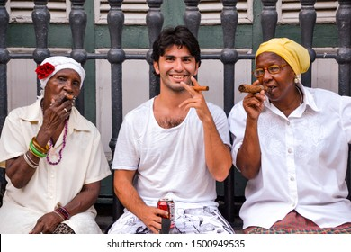 Havana/Cuba-10/07/2013: A tourist man smoking cuban cigar with cuban women and drinking Bucanero beer. If you don't drink Rom,Mojito, Cubalibre or pina colada then Bucanero Beer is the drink.