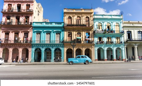 Havana,Cuba-December 2017: Vintage car and colonial houses build next to each other. Bright colour facade and old fashion vehicle in the streets of Havana. Local neighbourhood. Postcard background.