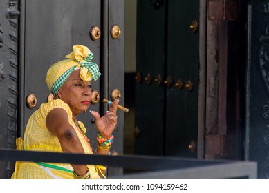 HAVANA-Feb 2018:Woman with typical clothes and a cuban cigar.People dress in a way that represents the cuban nationality can still be found in the streets of Old Havana