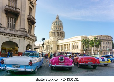 HAVANA-FEBRUARY 05: Old classic American cars parked in front of the Capitol  on February 05,2015 in Havana, Cuba. The Capitol is used as Cuban parliament build in 1929