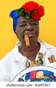 HAVANA-JUNE 29:Old black lady with a fine cigar June 29, 2011 in Havana. The african culture and religions have a huge influence in Cuba where approximately 50% of the population is of african descent