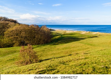 Havang, Sweden. Landscape view over grass covered sand dunes with the Baltic sea in the background on a sunny spring evening.