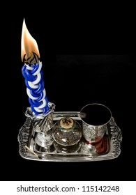 Havdala candle, kiddush cup, and spice set. The candle is lit after the conclusion of the Jewish sabbath; wine is served and a sweet spice is smelled. Isolated on a black background.