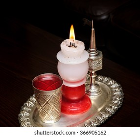 Havdalah candle wax . Silver cup with wine . Jewish ceremony Saturday night