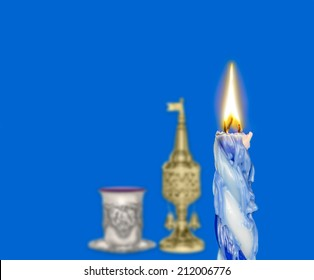 Havdalah set, focus on braided lit candle dripping wax. Jewish religious ritual objects for conclusion of Sabbath. Kiddush cup, red wine, metal spice container tower shape with bell and flag.