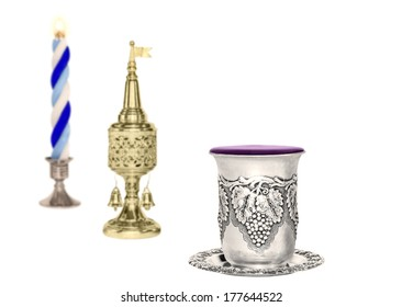 Havdalah set, selective focus on silver kiddush wine cup. Jewish religious ritual after conclusion of Sabbath. Braided lit candle. Gold color spice container, traditional tower shape with bell, flag.