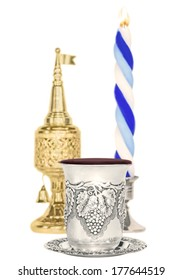 Havdalah set,selective focus on silver kiddush wine cup.Jewish religious ritual after end of Sabbath.Braided lit candle.Gold color spice container,traditional tower shape with bell, flag.Vertical view