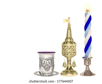 Havdalah set.Silver kiddush wine cup,gold color spice box,braided lit candle.Jewish religious ritual after end of Sabbath.Spice container,traditional tower shape,bell and flag.Horizontal photo.