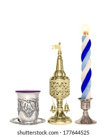 Havdalah set.Silver kiddush wine cup,gold color spice box,braided lit candle.Jewish religious ritual after end of Sabbath.Spice container,traditional tower shape,bell and flag.Vertical view.
