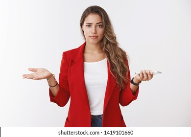 Have any problem. Questioned bothered attractive confident young caucasian curly-haired woman shrugging dismay unsure holding smartphone hands spread sideways, cannot understand what person want