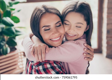 I have the best mummy in the world! Close up portrait of happy joyful mother and cheerful daughter, they are hugging with closed eyes