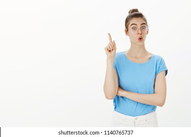 I have fantastic idea. Portrait of positive friendly european female in glasses, folding lips and raising index finger in eureka gesture, suggesting great solution or plan, sharing thoughts with team