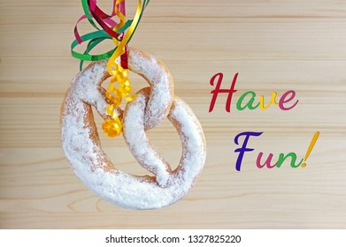 Have fun, carnival background with sweet pretzel and multi colored streamers in front of bright wood