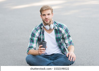 Have fun during break. Guy carefree student enjoy coffee outdoors. College life. Life balance. Wellbeing and health. Having coffee break. Man sit on ground while drinking coffee. Relax and recharge.