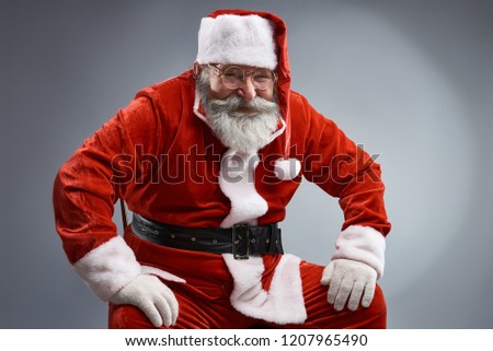 f8abf8d2d9f Studio portrait of smiling old man in Santa costume posing on gray