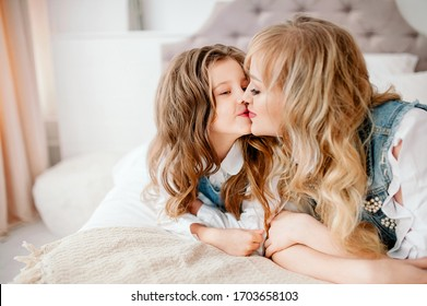 Have a good time at home. Mom kisses daughter on the bed in the bedroom.