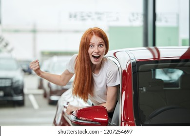 I have got it. Happy excited ginger hair woman buying a new car. Female customer can not hide delight and admiration with her purchase and screaming loudly out of her car salon.