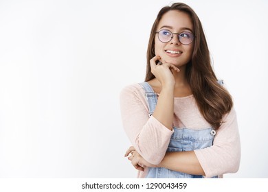 I have great plan. Portrait of smart and creative female freelance programmer in glasses smiling delighted and touching jaw, looking left curiously as having idea or interesting thought over gray wall