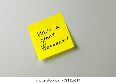 have a great weekend note on yellow paper sticker on a white fridge close-up
