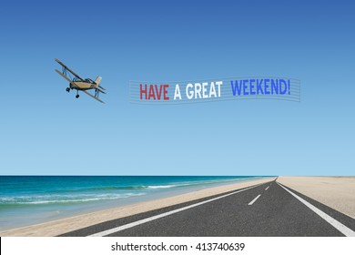 have a great weekend plane banner in american flag colors of red white and blue flying over road at beach