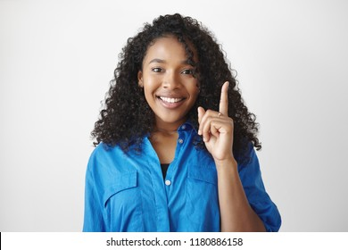 I have an idea. Cheerful cute African student girl with voluminous hair smiling excitedly and raising fore finger, full of great ideas while working on her home assignment, thinking outside the box