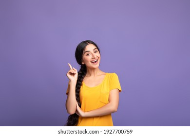 I Have An Idea. Portrait of cheerful young indian woman having great thought, finding inspiration or solution to problem. Positive lady pointing finger up isolated over purple studio wall, copy space