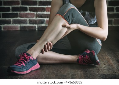 have a leg cramp in fitness exercise training, healthy lifestyle concept, indoors gym wooden floor brick wall background