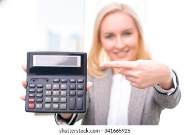 Have a look. Close up of calculator in hands of professional positive businesswoman holding it and pointing it out while being busy at work