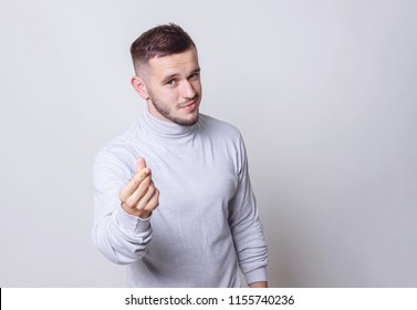 Have a money concept. Portrait caucasian man making cash sign gesture rubbing fingers together on grey background copy space