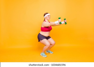 I have motivation and will-power! Cute positive cheerful fatty woman is doing deep squats with little green dumbbells, isolated on bright yellow background, copy-space
