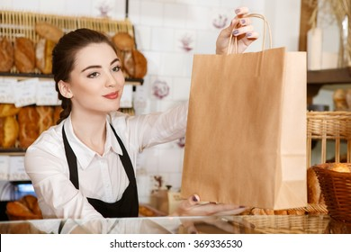 Have a nice day! Horizontal portrait of a gorgeous female baker passing paper bag with bread to the customer