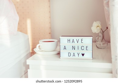 Have a nice day text message on lighted box, cup of coffee and white flower on the bedside table in sun light. Good morning mood. Hospitality, care, service concept. Selective focus. Copy space