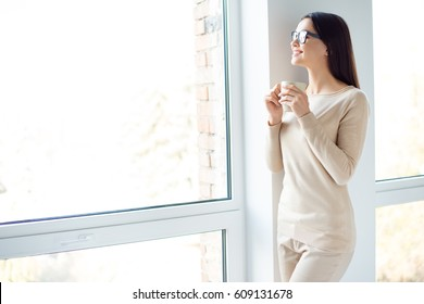 Have a nice day! Young smart successful smiling woman in glasses having break, holding cup and drink coffe while standing near window and dreaming.