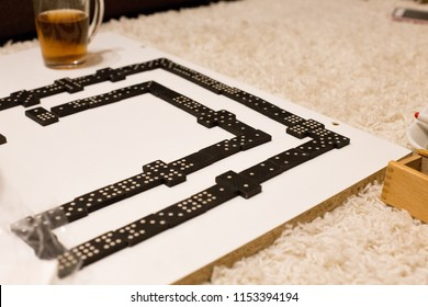 Have a nice time in evening with friends, Playing dominoes on a white board. Domino pieces on the white wooden table background. Fruits, glass cup of tea, empty dirty plate. Close up. Board games.