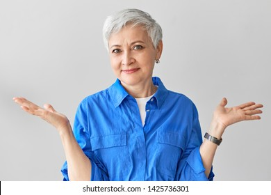 I have no idea. Stylish emotional middle aged mature female with short gray hair expressing confusion, shrugging her shoulders, being perplexed and at loss, saying I don't know. Body language