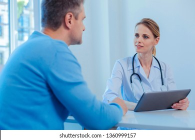 I have a problem. Competent doctor sitting at her workplace opposite patient and having stethoscope around neck while talking to him