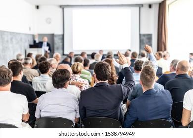 J'ai une question. Groupe d'hommes d'affaires assis aux chaises dans la salle de conférence. Homme d'affaires levant le bras. Conférence et présentation. Business et Entrepreneuriat.
