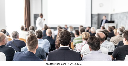 Ich habe eine Frage. Gruppe von Geschäftsleuten, die auf den Stühlen im Konferenzsaal sitzen. Geschäftsmann, der eine Frage stellt. Konferenz und Präsentation. Unternehmen und Unternehmertum.