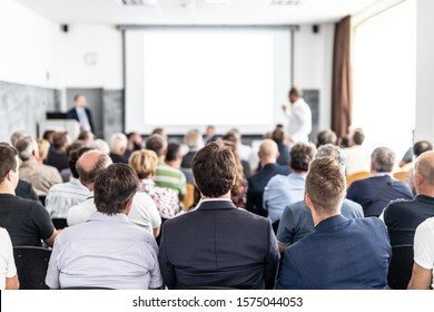 I have a question. Group of business people sitting at the chairs in conference hall. Businessman standing up asking a question. Conference and Presentation. Business and Entrepreneurship.
